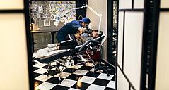 Woman receiving tattoo in tattoo studio - MGOF001101