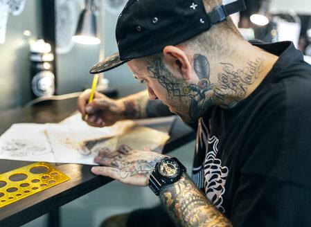 Tattoo artist designing motifs - MGOF001104