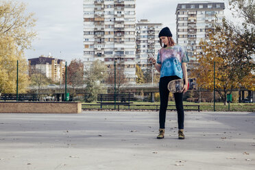 Young woman with skateboard looking at cell phone - ZEDF000019