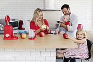Family of four in the kitchen preparing apple sauce together - LITF000013