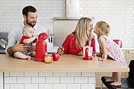 Family of four in the kitchen preparing apple sauce together - LITF000016