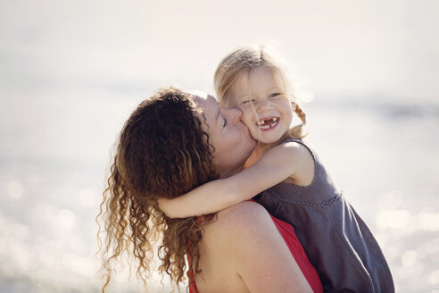 Mother kissing her little daughter with toothgap in front of the sea - LITF000037