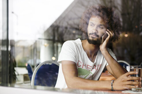 Portrait of pensive man sitting in a cafe telephoning with smartphone - GDF000909