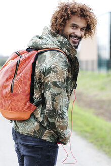 Portrait of man with dyed ringlets wearing camouflage jacket and backpack looking over his shoulder - GDF000915
