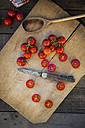 Slices and whole tomatoes, cooking spoon and a knife on chopping board - LVF004207