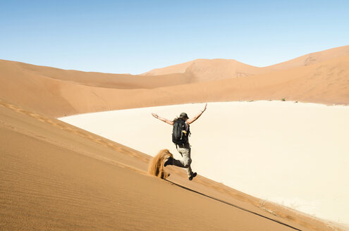 Namibia, Namib Desert, woman running down a dune on the way to Deadvlei - GEMF000510
