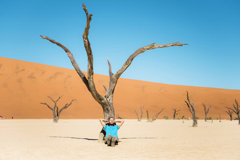 Namibia, Namib Desert, man resting at dead tree in Deadvlei - GEMF000513
