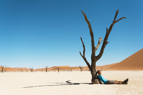 Namibia, Namib Desert, man resting at dead tree in Deadvlei - GEMF000516