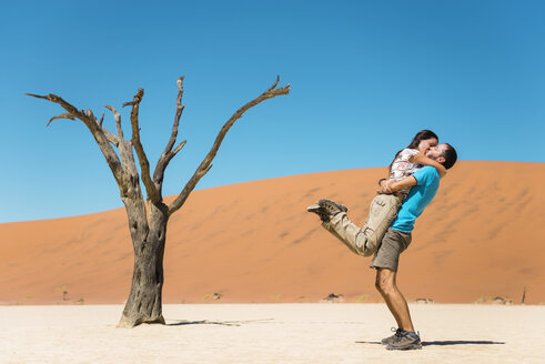 Namibia, Namib Desert, happy couple kissing next to dead tree in Deadvlei - GEMF000519