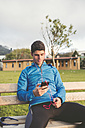 Athlete sitting on bench after training listening to music from smartphone - RAEF000689