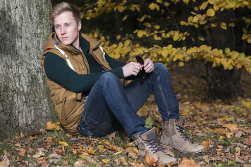 Young man sitting at tree in autumn - GDF000921