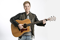 Smiling young man playing guitar - GDF000933