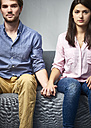 Serious young couple sitting on couch holding hands - DISF002263