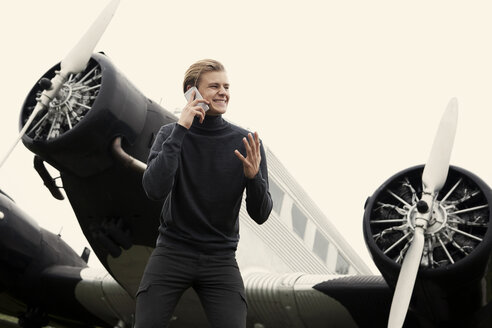 Young man on cell phone in front of vintage propeller plane - TMF000075