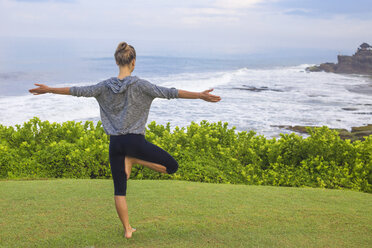 Indonesia, Bali, Tanah Lot, woman practising yoga at the coast - KNTF000185