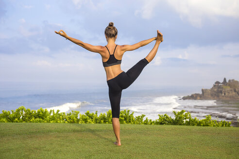 Indonesia, Bali, Tanah Lot, woman practising yoga at the coast - KNTF000188