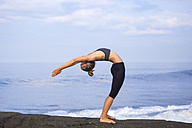 Indonesia, Bali, woman practising yoga at the coast - KNTF000191