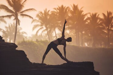 Indonesia, Bali, woman practising yoga at the coast at twilight - KNTF000194