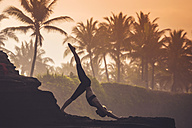 Indonesia, Bali, woman practising yoga at the coast at twilight - KNTF000197
