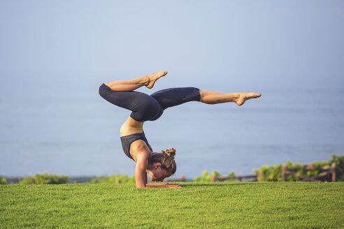 Indonesia, Bali, woman practising yoga on lawn - KNTF000200