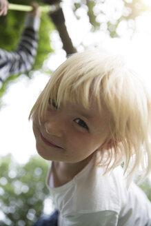 Portrait of smiling blond girl outdoors - FKF001605