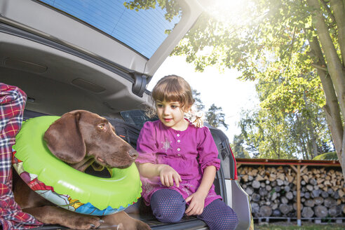 Girl in car boot with dog wearing floating tyre - FKF001617