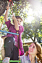Mother watching daughter on rope ladder in garden - FKF001623