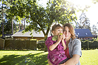 Mother holding daughter with apple in garden - FKF001629