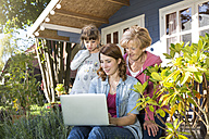 Grandmother, mother and daughter looking at laptop on garden terrace - FKF001644