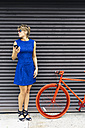 Woman with smartphone and red racing cycle waiting in font of roller shutter - GIOF000548
