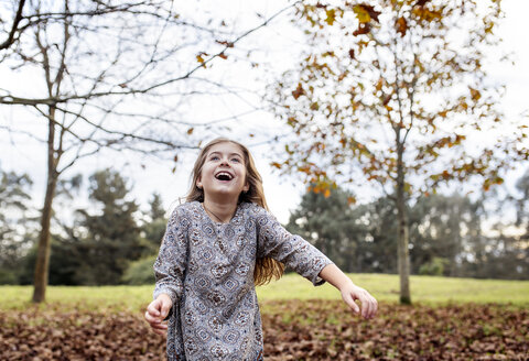 Happy girl throwing autumn leaves in the air - MGOF001114