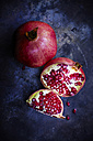 Sliced and whole pomegranate on dark ground - KSWF001684