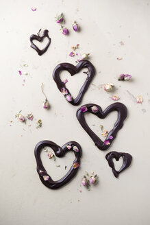 Chocolate hearts and dried rose blossom on light ground - MYF001256