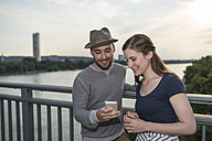 Germany, Bonn, young couple standing on Rhine bridge looking at smartphone - PAF001497