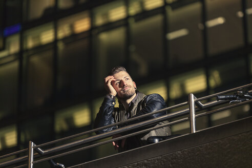 Germany, Berlin, portrait of man looking at distance in front of lighted office building - MMFF001280