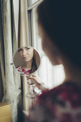 Young woman looking in hand mirror - MAUF000124