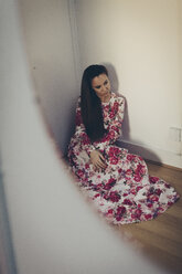 Young woman in floral dress in corner of a room - MAUF000127