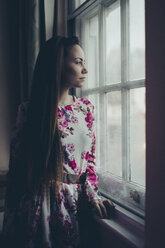 Young woman in floral dress looking out of window - MAUF000130