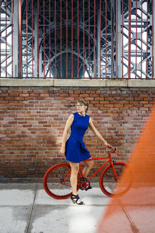 USA, New York City, Williamsburg,  blond woman with red racing cycle - GIOF000564