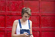 Blond woman in front of red background looking at her smartphone - GIOF000567
