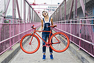 USA, New York City, Williamsburg,  woman with red racing cycle on Williamsburg Bridge - GIOF000579