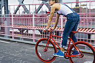 USA, New York City, Williamsburg,  woman riding red racing cycle on Williamsburg Bridge - GIOF000582