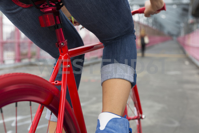 Legs of woman on red bicycle, close-up - GIOF000585