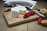 Camembert, bread and red currants on wood - LVF004239