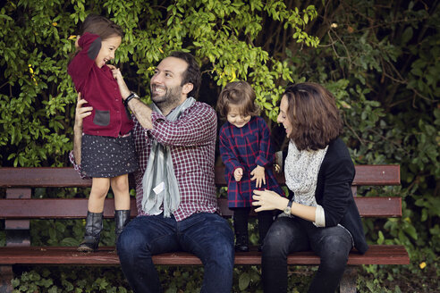 Laughing parents sitting on a bench tickling their little daughters - LITF000074
