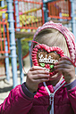 Girl holding gingerbread heart with German inscription - GSF001011