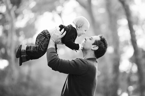 Smiling father holding baby boy in the air - LITF000090