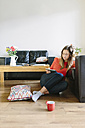Young woman sitting on the floor of her living room looking at digital tablet - BOYF000018