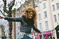 Ireland, Dublin, smiling woman with afro balancing - BOYF000029