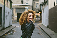 Ireland, Dublin, smiling woman with afro looking over her shoulder - BOYF000032